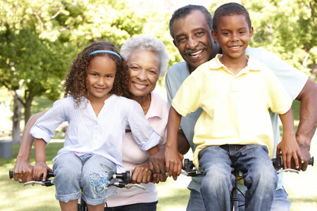 riding: African American Grandparents With Grandchildren Cycling In Park