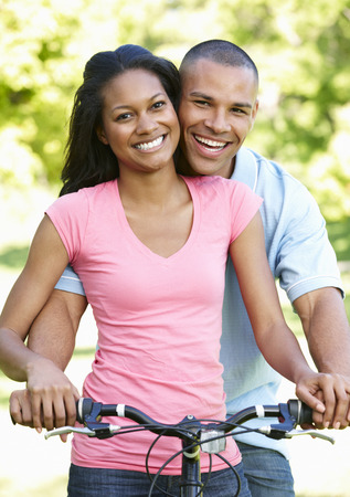Young African American Couple Cycling In Park Stock Photo