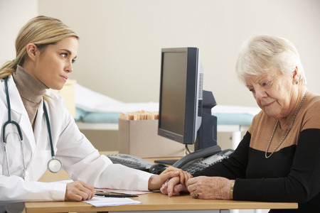 adult 80s: Doctor reassuring senior woman patient Stock Photo