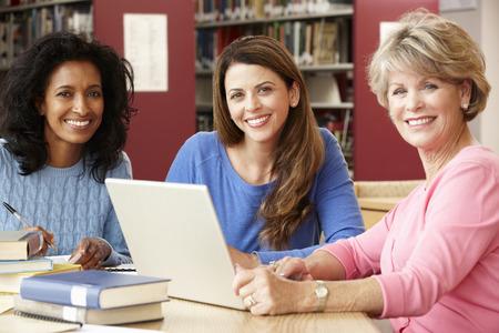 Rijpe studenten die in bibliotheek Stockfoto