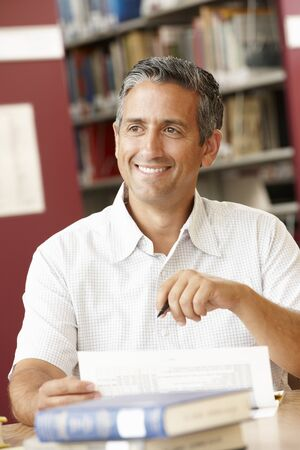 coursework: Mature student working in library Stock Photo