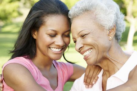 mother and daughter: Madre africana americana e hija adulto que se relaja en el parque
