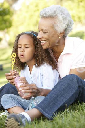アフリカ系アメリカ人の祖母と孫娘の公園でシャボン玉を吹く 写真素材
