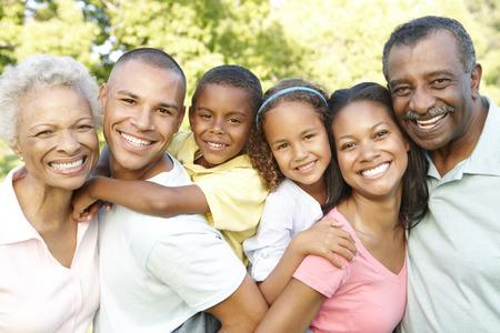 personas felices: Familia del afroamericano Multi Generaci�n relaja en parque Foto de archivo