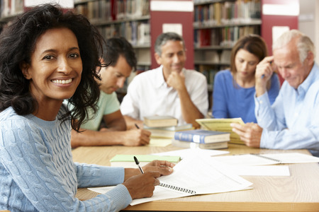 female student: Mature students working in library Stock Photo