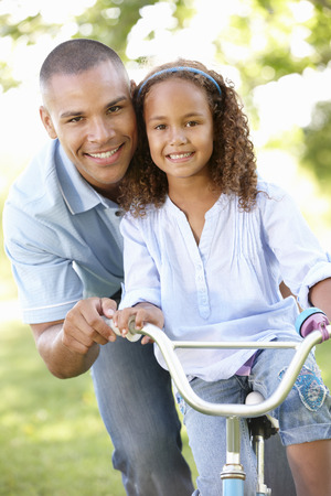father teaching daughter: Father Teaching Daughter To Ride Bike In Park