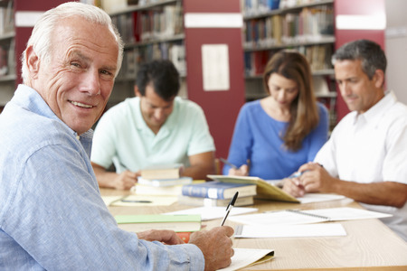 adult students: Mature students working in library Stock Photo