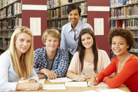 boy 15 year old: Group of students working in library with teacher Stock Photo