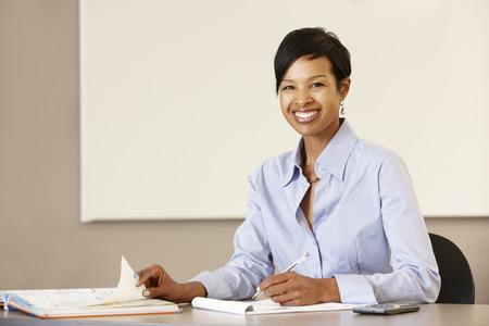 책상에서 일하고 흑인 교사