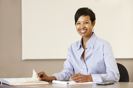 front desk: African American teacher working at desk