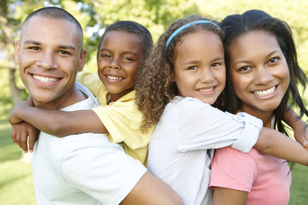 family park: Young African American Family Relaxing In Park Stock Photo