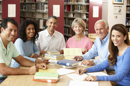 older women: Mature students working in library Stock Photo