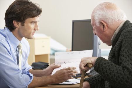 doctores: El doctor habla con el paciente de sexo masculino mayor Foto de archivo