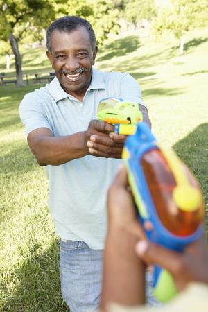 Afro-Amerikaanse grootvader en kleinzoon spelen met water pistolen in Park Stockfoto