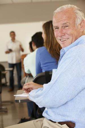 the elderly tutor: Mature student in class Stock Photo