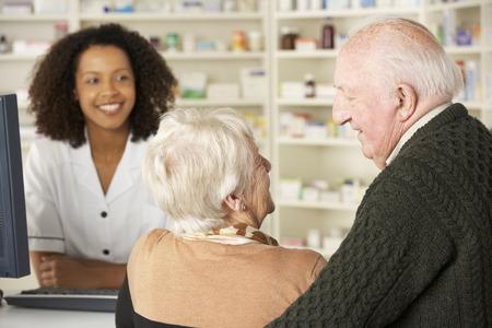 Pares mayores en la farmacia con el farmacéutico