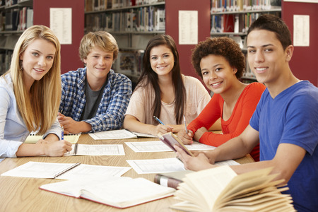 boy 15 year old: Group of students working together in library