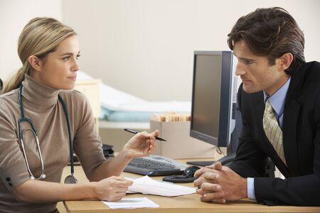 hombre de negocios: Doctora hablando de negocios paciente Foto de archivo