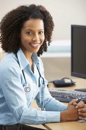 nhs: Young female Doctor sitting at desk