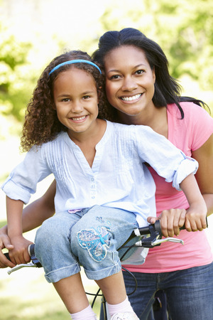 handlebars: Young African American Mother And Daughter Cycling In Park