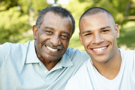 padre e hijo: Padre del afroamericano e hijo adulto que se relaja en el parque