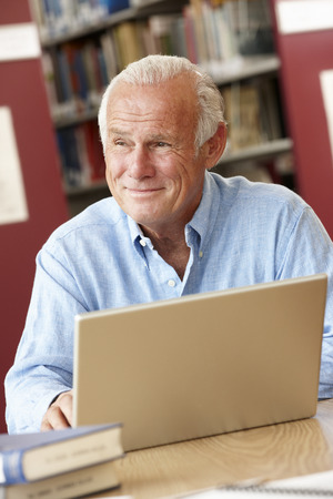 older men: Mature student working in library Stock Photo