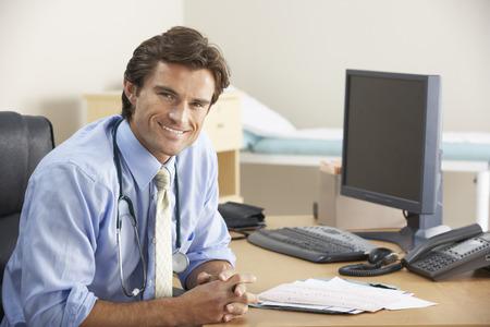nhs: Doctor sitting at desk