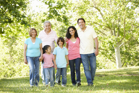 Multi Generation Hispanic Family Walking In Park