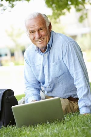 one person: Senior man using laptop outdoors