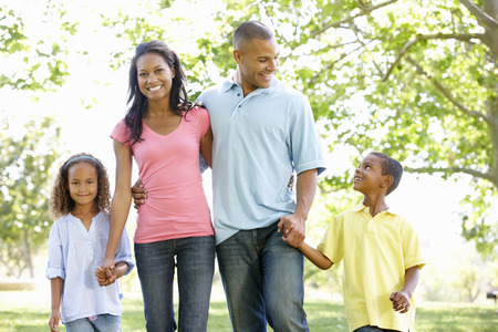 Young African American Family Enjoying Walk In Park Stock Photo