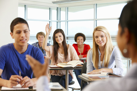 preguntando: Multi alumnos adolescentes raciales en una clase con la mano hacia arriba