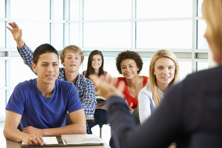 Multi racial teenage pupils in class one with hand up