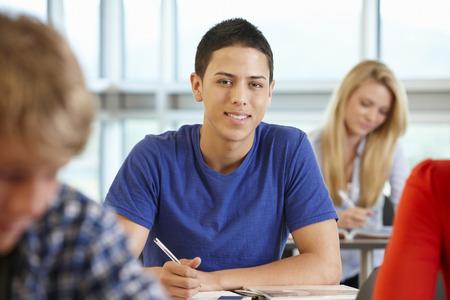 Spaanse tiener jongen in de klas lacht naar de camera
