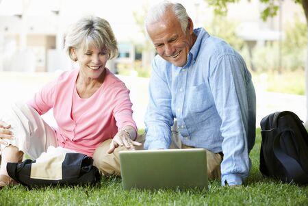 couple outdoor: Senior couple using laptop outdoors Stock Photo