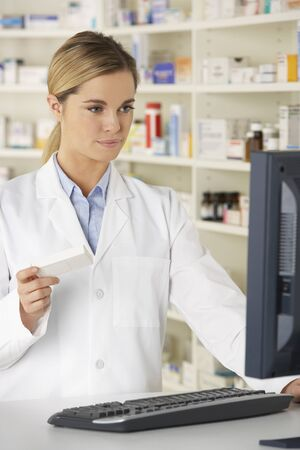 prescribed: Pharmacist working on computer in pharmacy