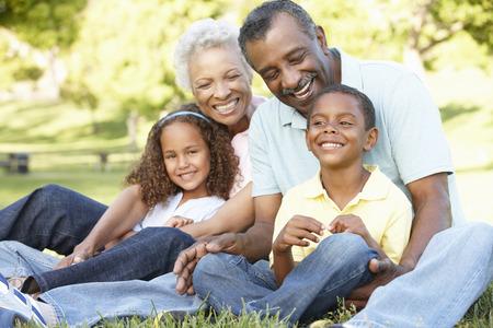 afroamericana: Abuelos afroamericanos con los nietos que se relaja en parque