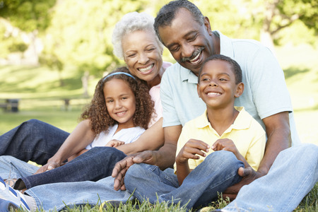 African American Grandparents With Grandchildren Relaxing In Park