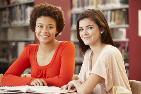 16 year old girls: 2 Students working together in library Stock Photo
