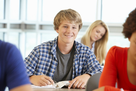 Teenage boy in class smiling to camera