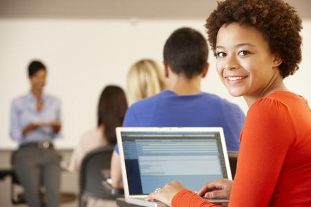 salle de classe: Métisse adolescente utilisant un ordinateur portable en classe Banque d'images