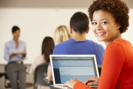 boy 15 year old: Mixed race teenage girl using laptop in class Stock Photo