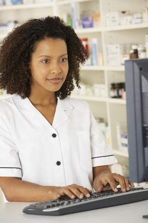 nhs: Nurse working on computer in pharmacy