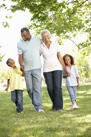 family outside: African American Grandparents With Grandchildren Walking In Park