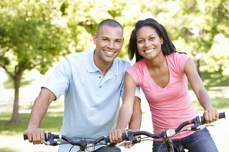 african american woman smiling: Young African American Couple Cycling In Park Stock Photo