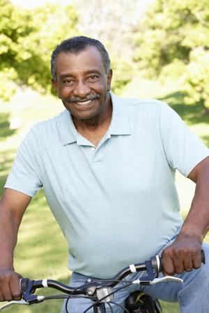 jubilados: Superior hombre del afroamericano que completa un ciclo en el parque