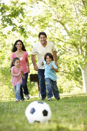 jugando: Familia hispánica joven que juega a fútbol en el parque