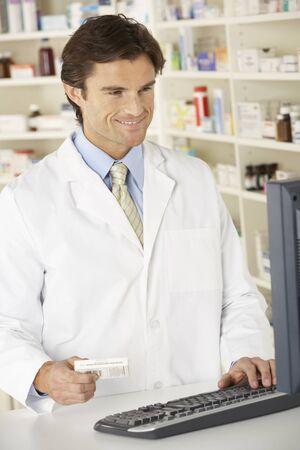 Pharmacist working on computer in pharmacy