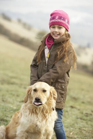 7 year old girl: Girl on country walk with dog in winter