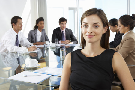 mixed age range: Businesswoman Sitting Around Boardroom Table With Colleagues Stock Photo