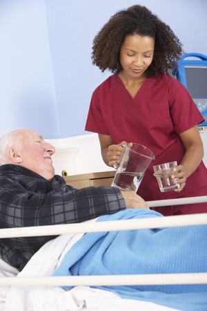 happy patient: Nurse giving glass of water to senior man in hospital
